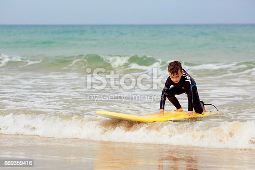istock Little boy with surf board learning surfing 669359416