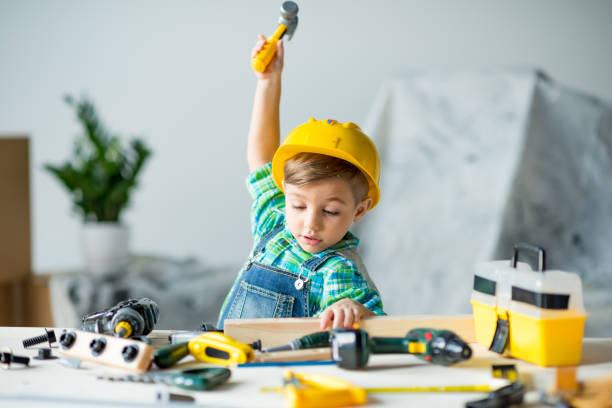 Little boy with tools Cute little boy in yellow hard hat holding wooden plank and toy hammer gardening equipment stock pictures, royalty-free photos & images