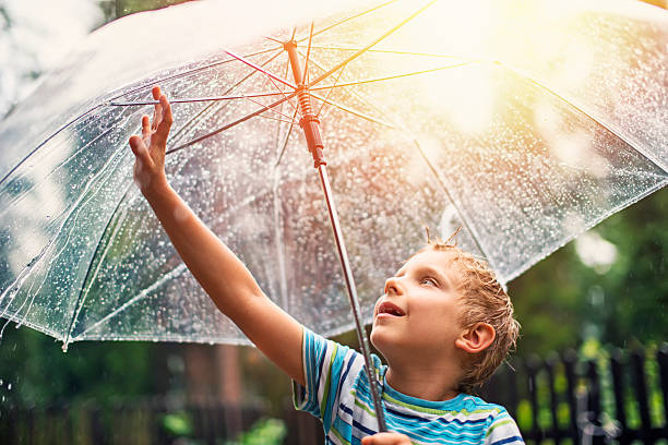 little boy with transparent umbrella enjoying rain. - regen zon stockfoto's en -beelden