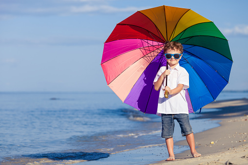 Little boy with umbrella standing on the beach