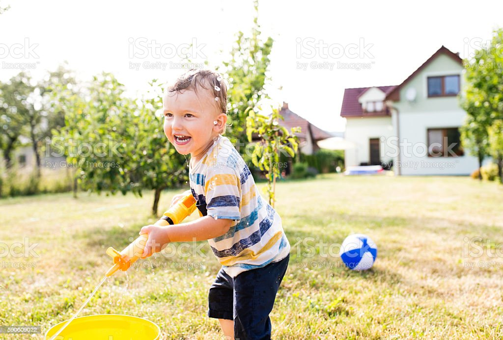Little boy with water gun splashing somebody, sunny summer garde stock photo