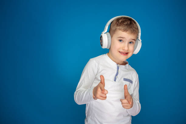 little boy with white headphones listening music stock photo