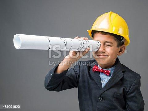 istock Little boy with yellow hardhat looking through blueprints as binoculars 481091920