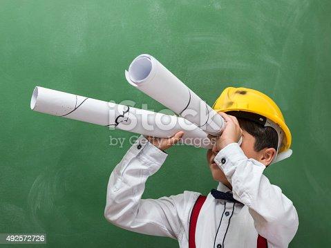 istock Little boy with yellow hardhat looking through blueprints as binoculars 492572726