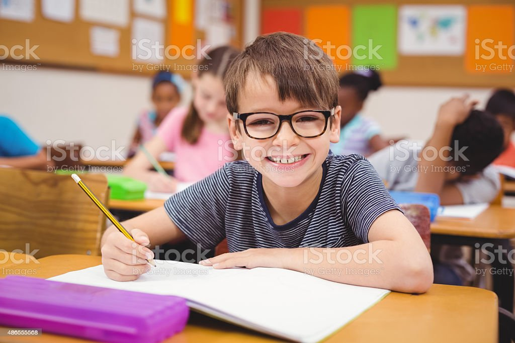 Little boy working at his desk in class stock photo