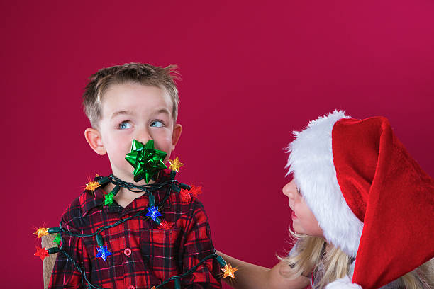 Little boy wrapped in Christmas lights stock photo