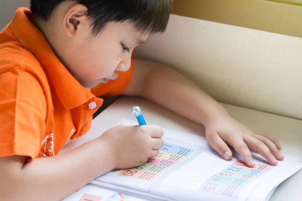 Niño escribiendo examen de matemáticas en casa. - foto de stock