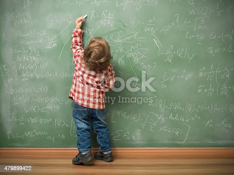 Little boy writing on green blackboard with math formulas written on.He is wearing a red plaid shirt and standing on the left side of frame.The green board is full of mathematics and physics formulas.He is seen in full length and holding chalk in left hand.The photo was shot in studio with a medium format camera Hasselblad H4D.