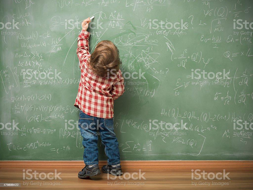 Little boy writing on green blackboard stock photo