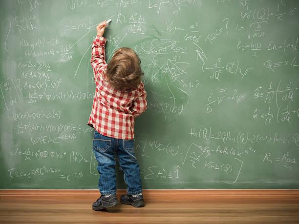 petit garçon écrit sur le tableau noir vert - gaucher photos et images de collection