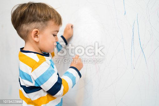Baby Boy Writing on the white wall in his room with crayons