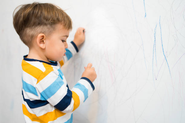 Little Boy Writing on the Wall Baby Boy Writing on the white wall in his room with crayons crayon stock pictures, royalty-free photos & images