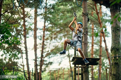 Little boy practicing in ropes course in adventure park. The boy is ziplining on sunny summer day. Nikon D850