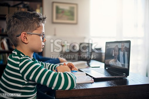 Little boys attending to online class from home. The school has been closed during coronavirus outbreak and the classes have moved to e-learning platform. Shot with Nikon D850