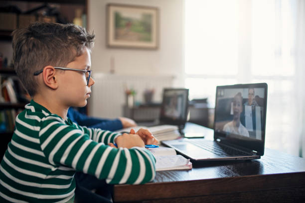 little boys attending to online school class. - quarantena foto e immagini stock