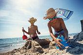 Brothers are having fun building a sandcastle on a beach on a sunny summer day.\nNikon D850