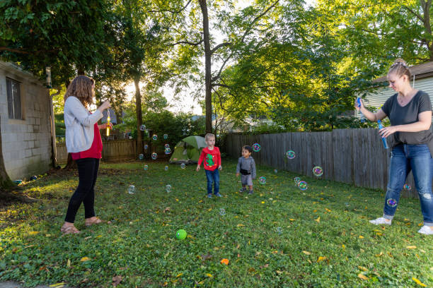 2 kleine Jungen jagen Blasen während einer Familienparty in einem Vorort Hinterhof – Foto