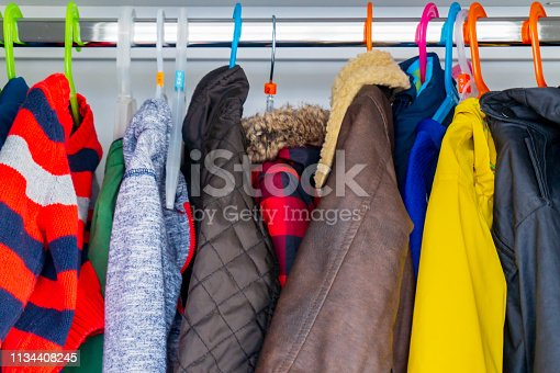 Little boy's child size jackets, coats and sweaters hanging in a kid's closet with colorful hangers.