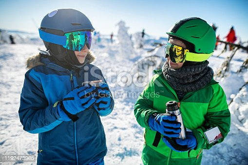 Mother with kids are enjoying skiing together. Family is taking a break to warm themselves with hot tea. Little boys drinking tea. Sunny winter day. Nikon D850