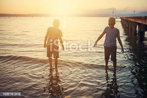 Little boys enjoying sunset at Garda Lake. Boy are wading in shallow water near a pier. Nikon D850