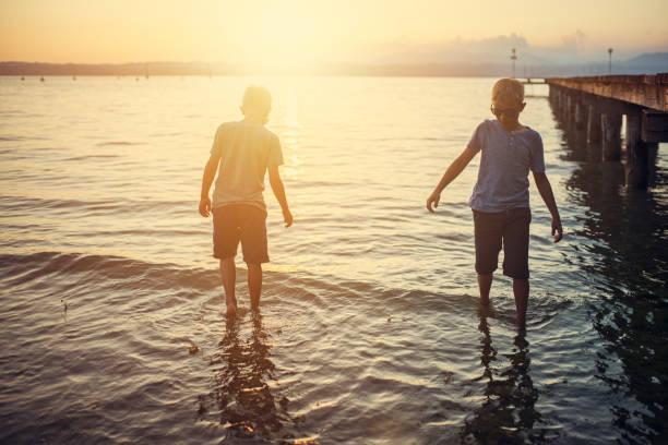 Little boys enjoying sunset at Garda Lake, Italy Little boys enjoying sunset at Garda Lake. Boy are wading in shallow water near a pier. Nikon D850 wading stock pictures, royalty-free photos & images