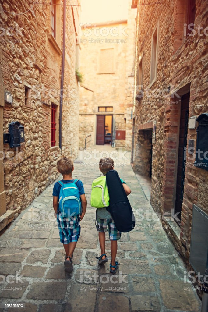 Little boys going to school in small italian town. stock photo