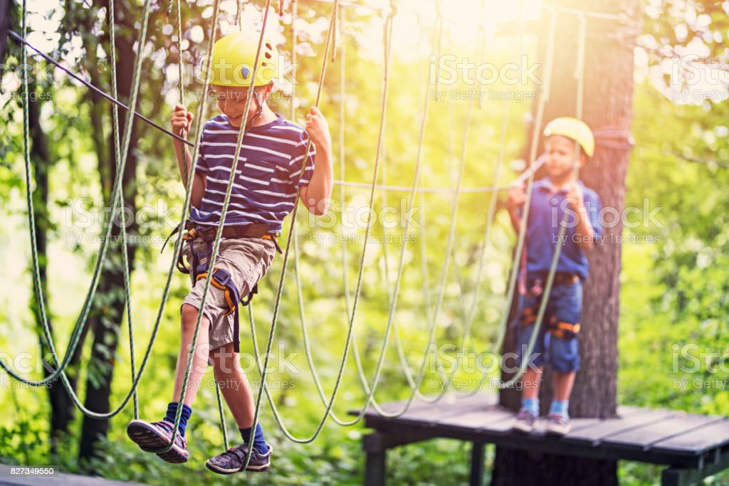 Little boys having fun during in ropes course  adventure park stock photo