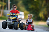 Two small boys enjoying while driving their vehicles outdoors.