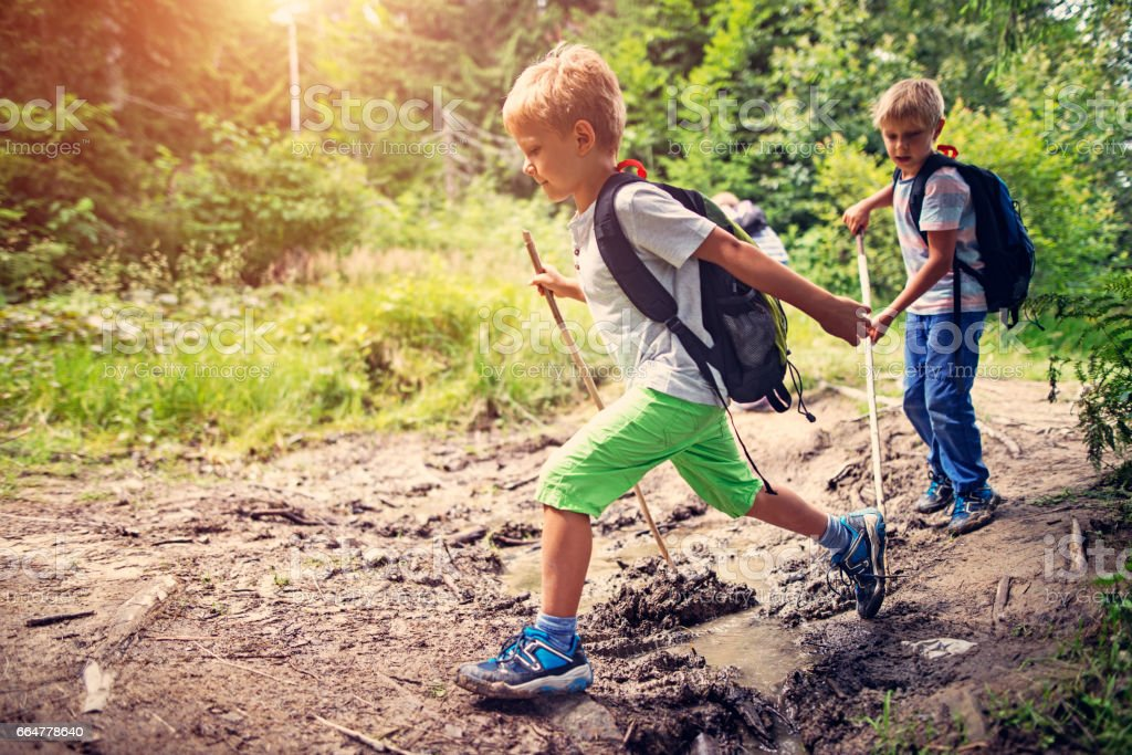 Little boys hiking on muddy path in forest stock photo