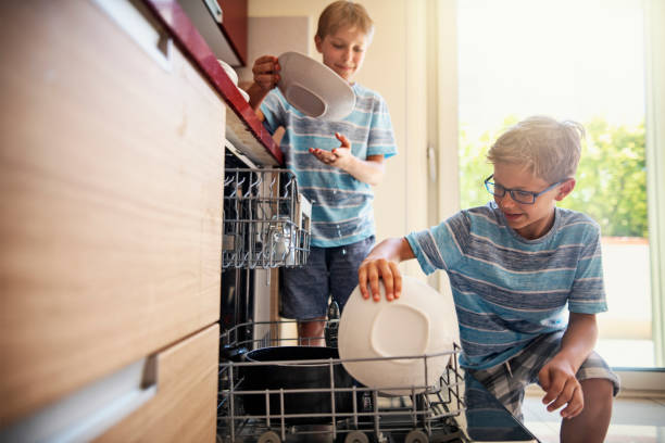 Little boys loading dishwasher after lunch Two boys helping in kitchen. The boys are working together loading the dishwasher with dishes. Nikon D850 dishwasher stock pictures, royalty-free photos & images