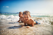 Little brothers aged 6 are having fun lying on beach and being splashed by waves. Sunny summer day in Playa de Muro, Spain, Mallorca