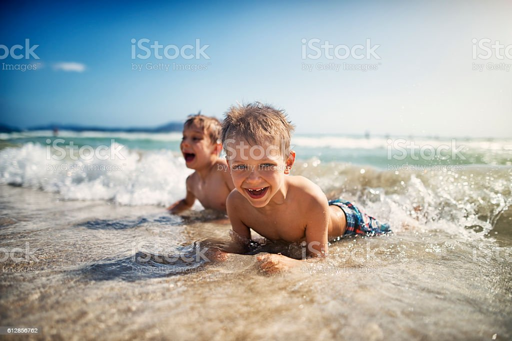 Little boys lying on beach in sea and laughing stock photo