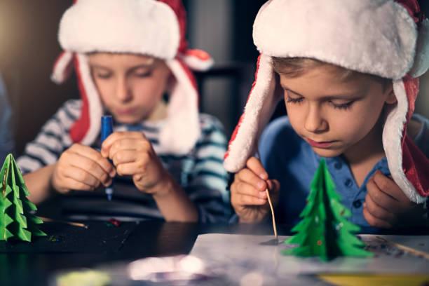 kleine jungs machen weihnachtsdekoration/papier - basteln mit kindern weihnachten stock-fotos und bilder