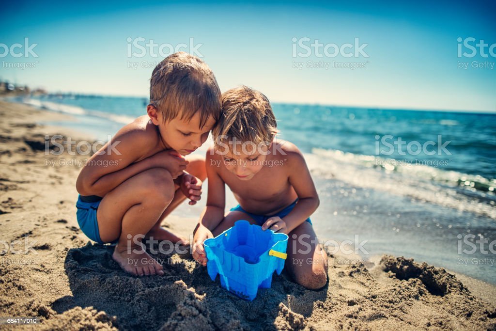 Little boys observing a fish caught in sand bucket stock photo