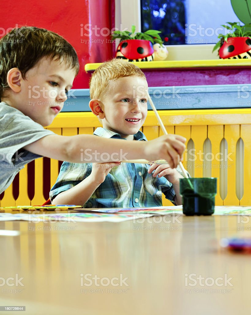 Little Boys Painting Two preschool boys sitting at the table in classroom and painting.  4-5 Years Stock Photo