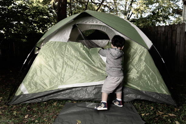 2 Kleine Jungs spielen zusammen in ihrem Hinterhof in einem grünen Campingzelt – Foto