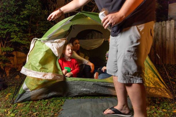 2 Kleine Jungs spielen zusammen mit ihren Müttern in ihrem Hinterhof in einem grünen Campingzelt in der Nacht – Foto
