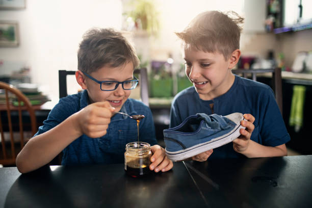 Little boys playing an April fools day prank Little boys playing an April fools day prank. The boys are pouring honey to a shoe.  Nikon D850 april fools day stock pictures, royalty-free photos & images