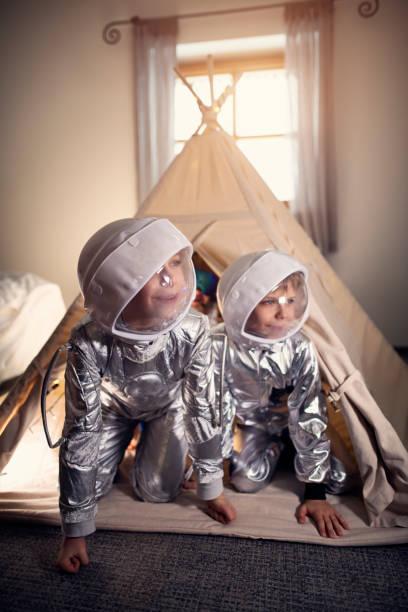 kleine jungs spielen astronauten in ihrem zimmer - tipi zelt stock-fotos und bilder