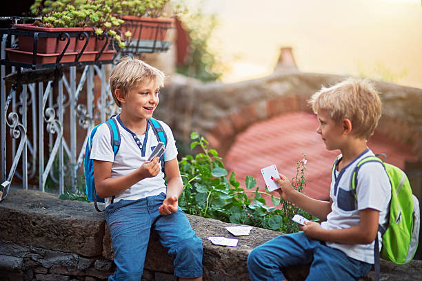 Little boys playing cards on their way to school Happy little boys playing cards on a small wall. They don't mind they will skip some classes if they play too long. absentee stock pictures, royalty-free photos & images