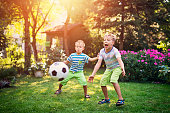 Little boys aged 7 are playing football in the garden.