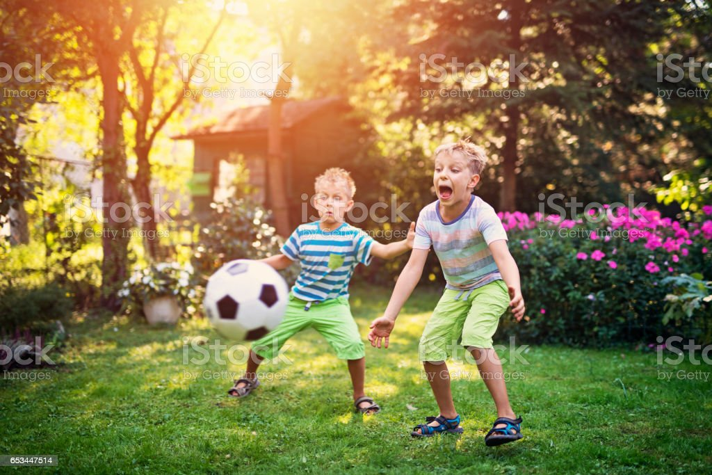Little boys playing football in the garden stock photo