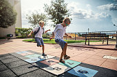 Laughing little boys playing  hopscotch in schoolyard. Nikon D850
