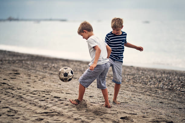 Little boys playing soccer on on beach stock photo