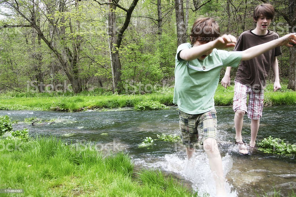 Little Boys Playing Splashing in Stream- Wooded Green Park stock photo