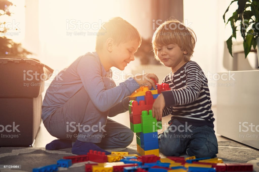 Little boys playing with blocks on the floor at home stock photo