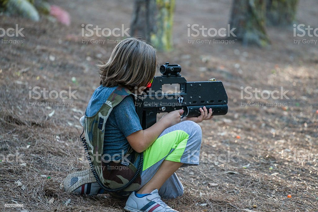 Little boys playing with gun during laser tag stock photo