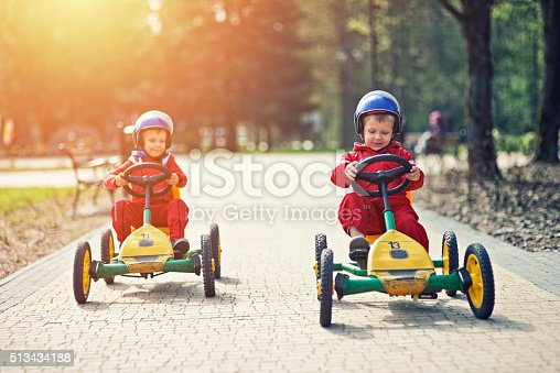 1035136022istockphoto Little boys racing on pedal go-karts 513434188