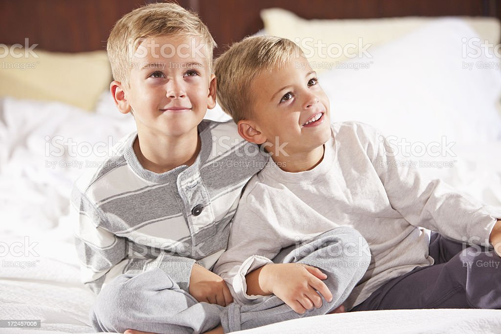 Little boys sitting on bed looking up stock photo