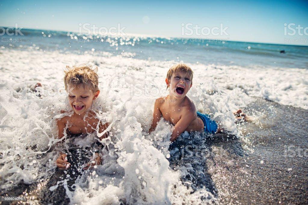 Kleine Jungs planschen in den Wellen des Meeres in der Toskana – Foto
